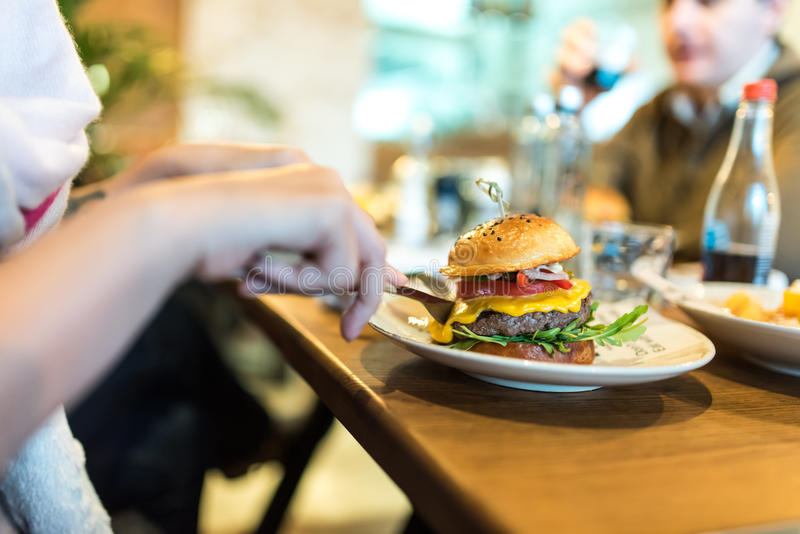 Woman eating burger with melted cheese royalty free stock image