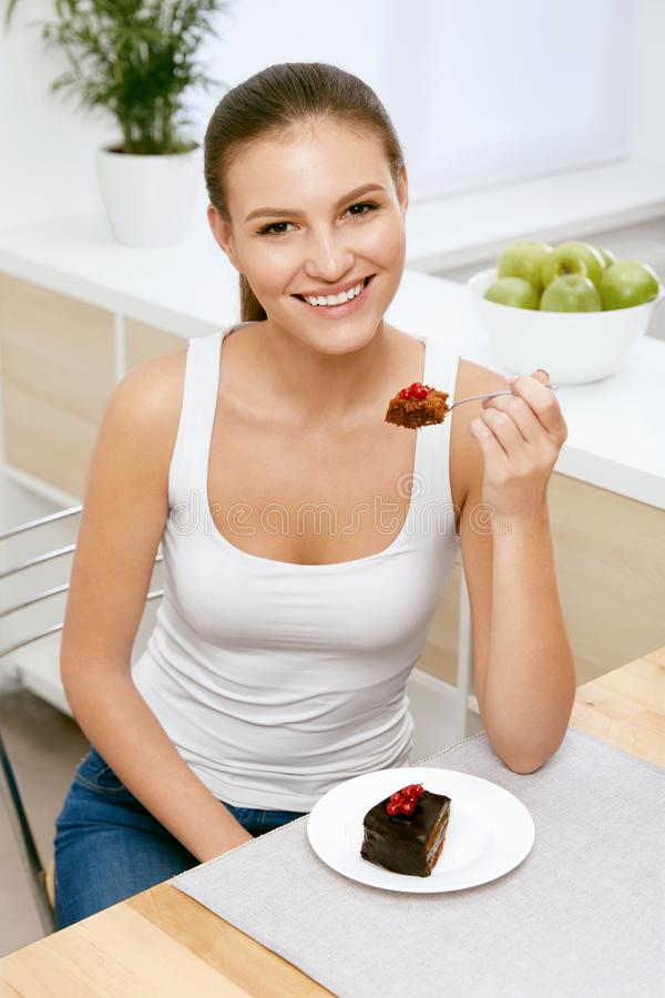 Woman Eating Cake. Beautiful Female Eating Dessert. Portrait Of Happy Smiling Young Woman Biting Piece Of Chocolate Cake. Sweets And Food Concept. High Quality royalty free stock image