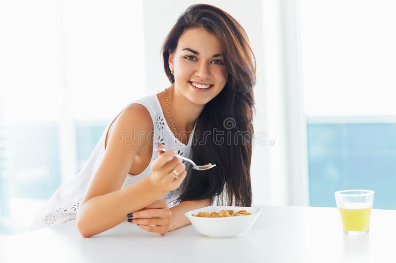Woman eating cereal and smiling at the camera. Attractive brunette woman eating bowl of cereal and smiling at the camera in the kitchen at home royalty free stock photos