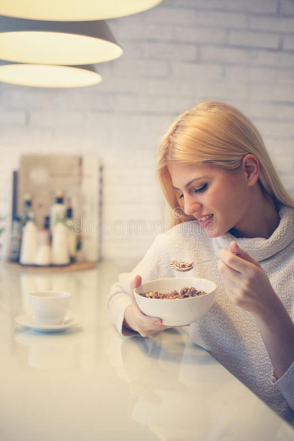 Woman eating cereals for breakfast. royalty free stock images
