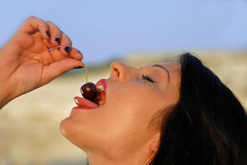 Woman eating a cherry. Woman is eating a cherry stock image