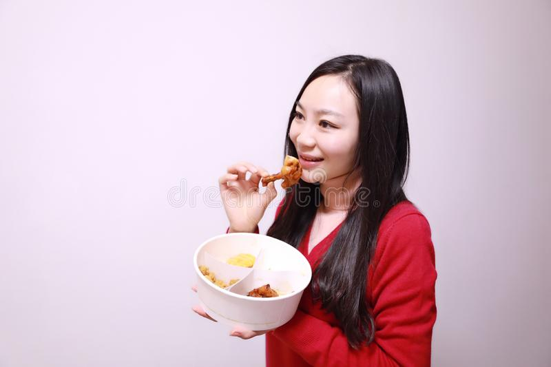 Woman eating chicken meat royalty free stock photos