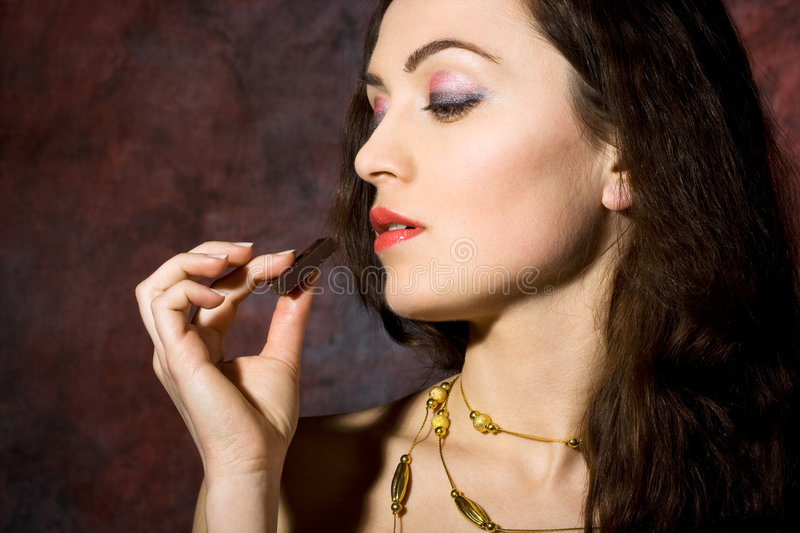 Woman eating chocolate. Young beautiful woman eating chocolate stock images