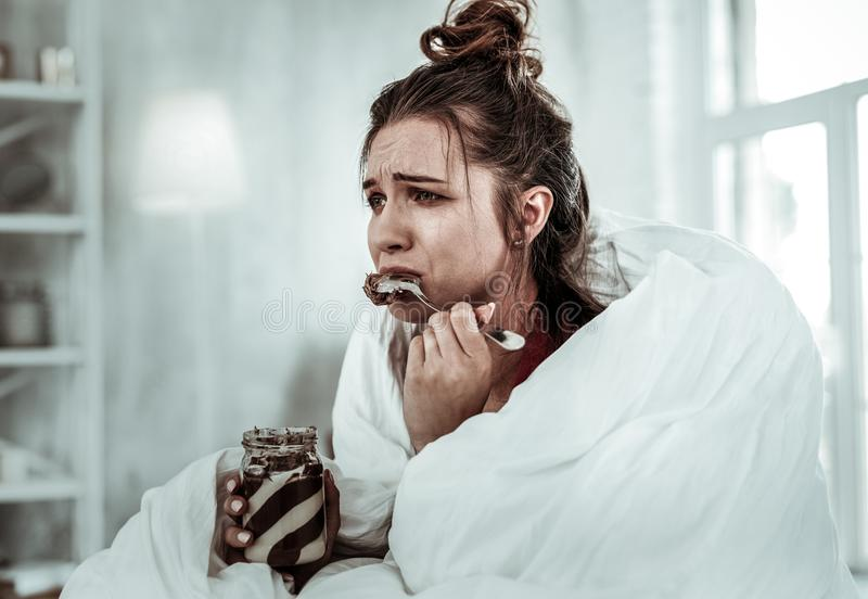 Woman eating chocolate pasta because of being stressed royalty free stock photography