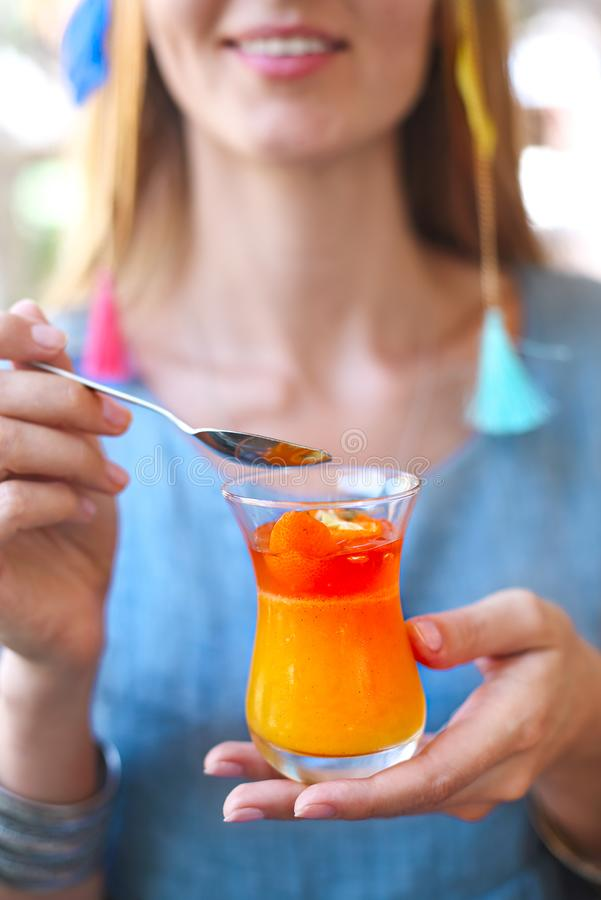 Woman eating citrus cumquat jelly dessert stock photo