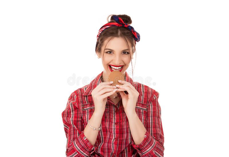 Woman eating cookie smiling happy. Isolated over white background looking at you camera stock photography