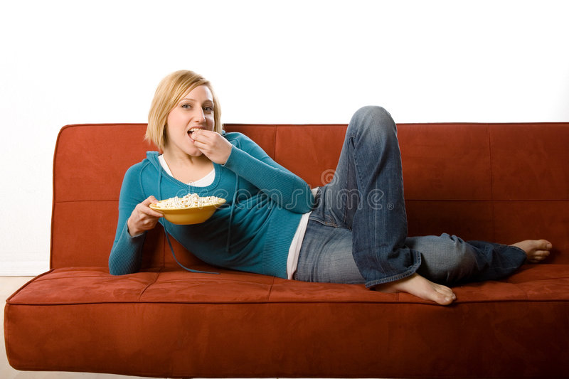 Woman eating on couch. A young woman in casual clothes lies on a couch eating popcorn. There's a white background. Woman is 29 royalty free stock image