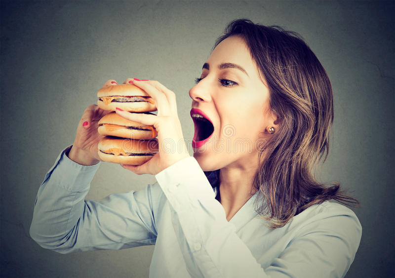 Woman eating craving a double burger royalty free stock photo