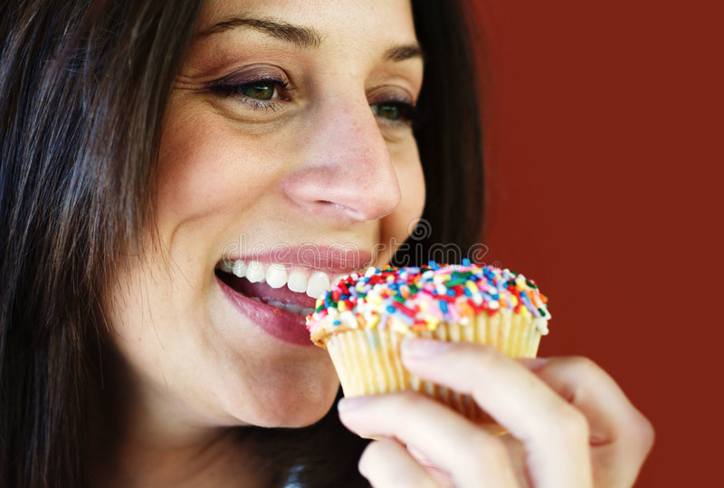 Woman eating cup cake royalty free stock photos