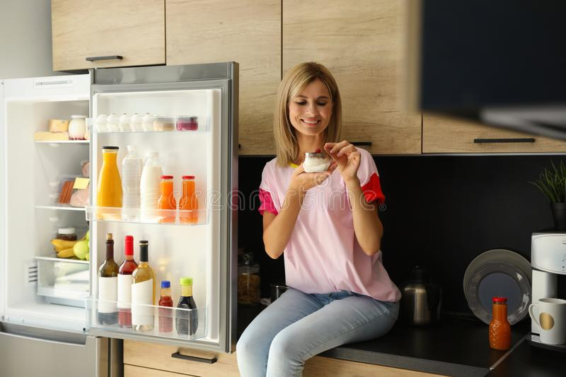 Woman eating dessert near refrigerator. In kitchen stock images