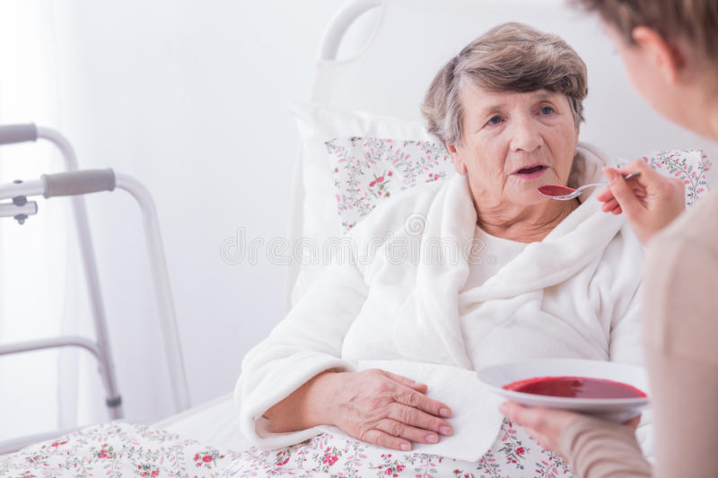 Woman eating dinner. Older sick women eating dinner with caregiver's help royalty free stock photography