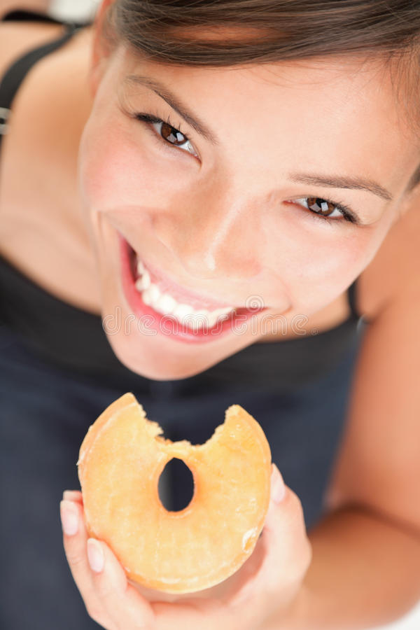 Woman eating donut junk food fun stock photo