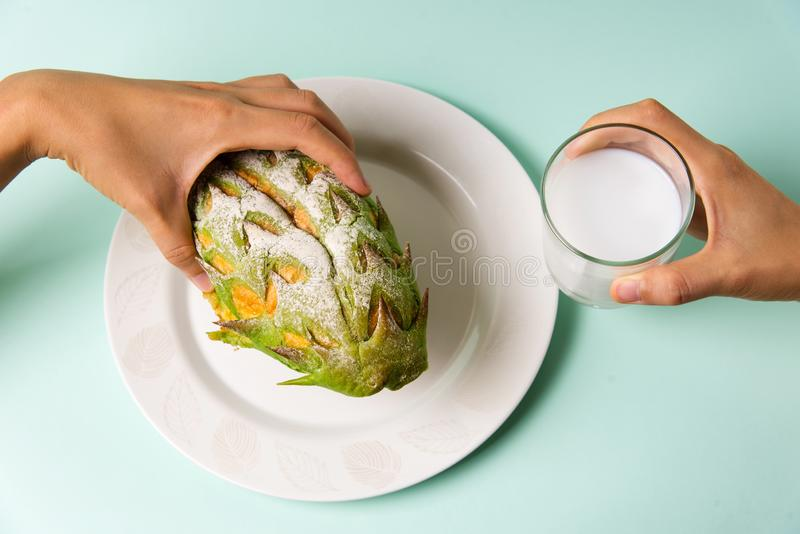 Woman eating durian shaped fruit bread stock photo