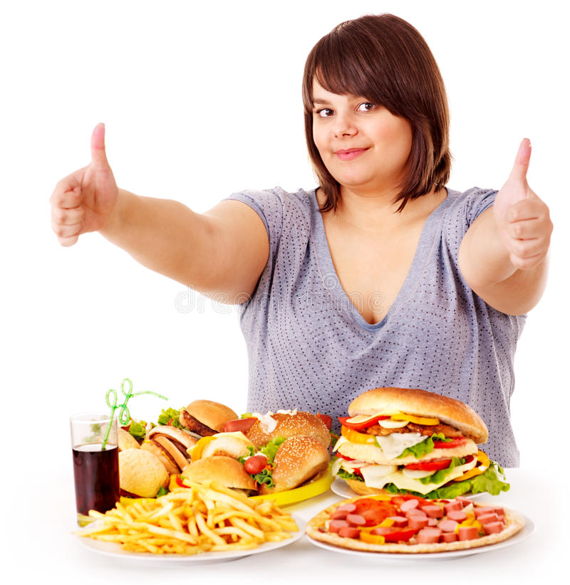 Woman eating fast food. Happy overweight woman eating fast food stock photography