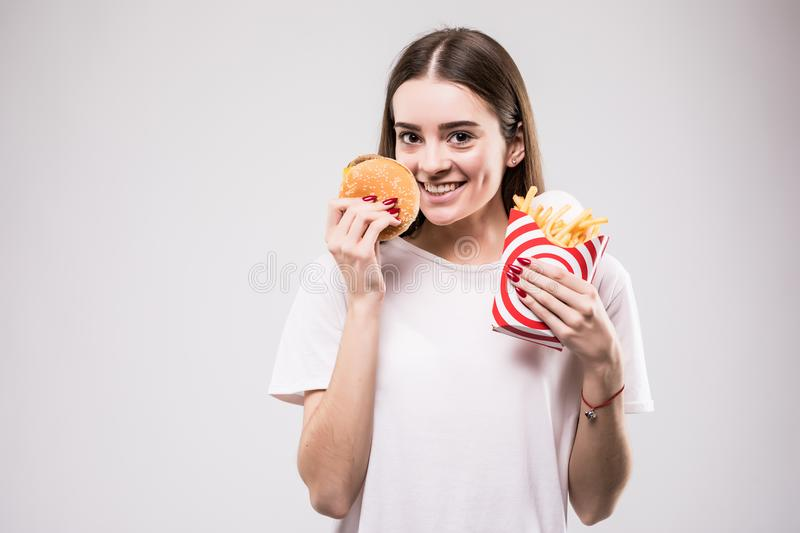 Woman eating fast food burger with french fried on gray background portrait. Health concept stock photo