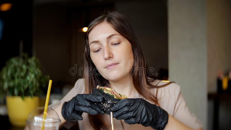 Woman eating fast food chicken burger at restaurant.  stock photography