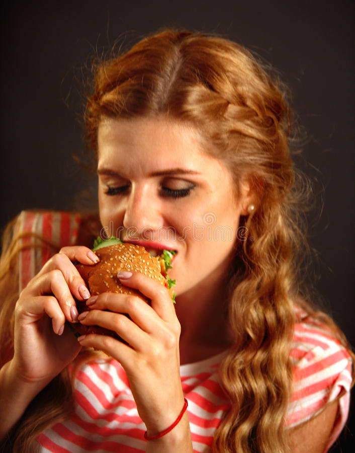 Woman eating fast food . Girl enjoying delicious hamburger. Woman eating fast food . Girl enjoying delicious hamburger, eyes closed. Pretty female student with stock images