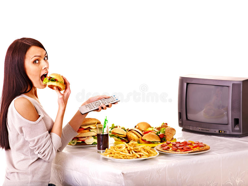 Woman eating fast food and watching TV. Isolated royalty free stock photo