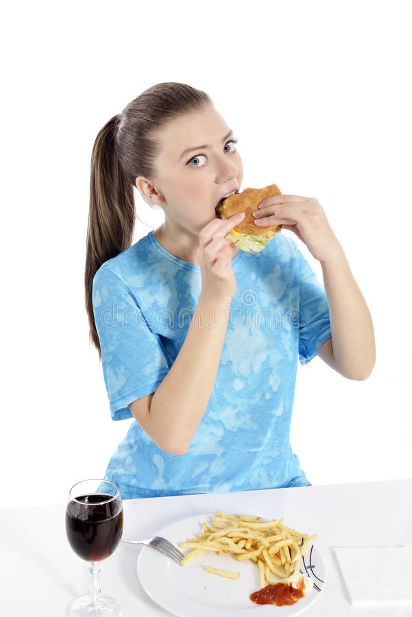 Woman eating fast food. Young woman eating fast food. beautiful girl hungry stock photo
