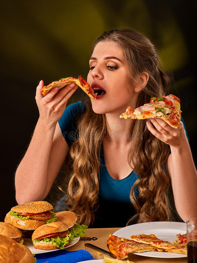 Woman eating french fries and hamburger with pizza. Portrait of student consume fast food on table. Cook teaches to cook and shares recipes. Girl eagerly eats royalty free stock image