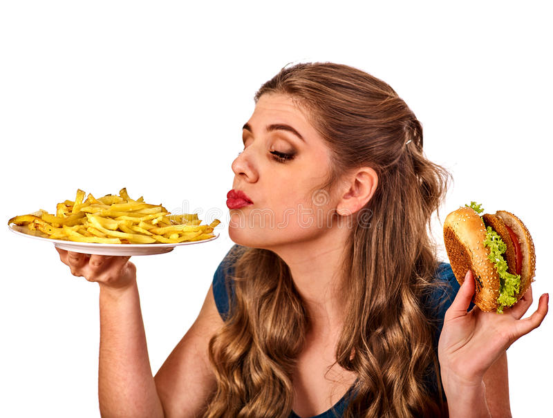 Woman eating french fries and hamburger on table. Woman eating french fries and hamburger. Portrait of student consume fast food on table. Girl trying to eat stock images