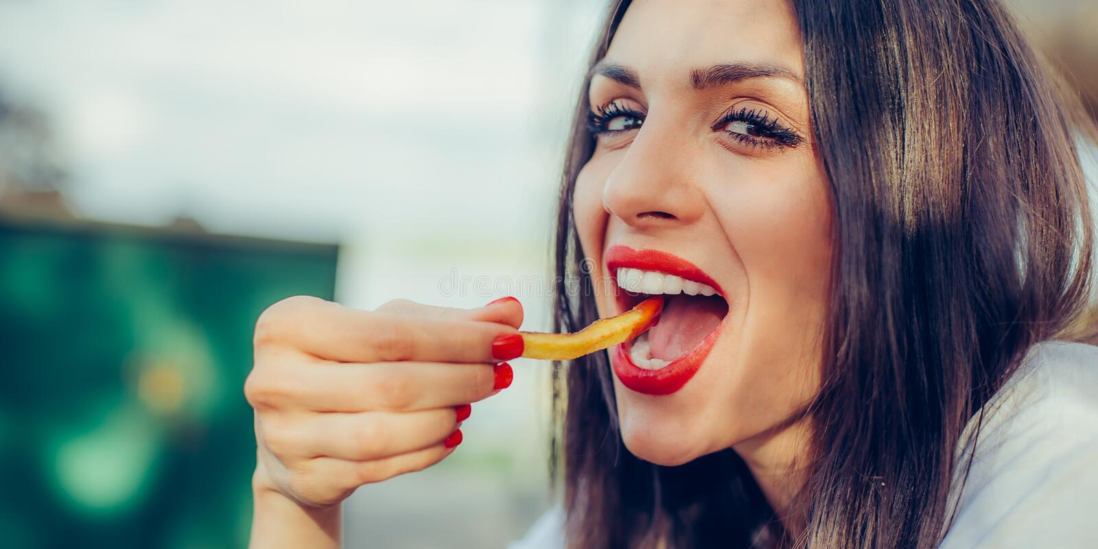 Woman eating french fries potato with ketchup in a restaurant. Young woman eating french fries potato with ketchup in a restaurant, having her lunch break. Close stock photo