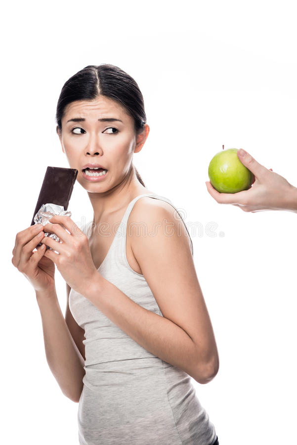 Woman eating a fresh apple while looking at chocolate royalty free stock images