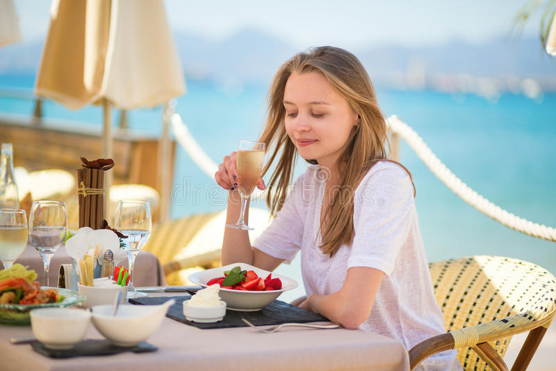 Woman eating fruits in a beach restaurant. Beautiful young woman eating fruits in a beach restaurant royalty free stock photo