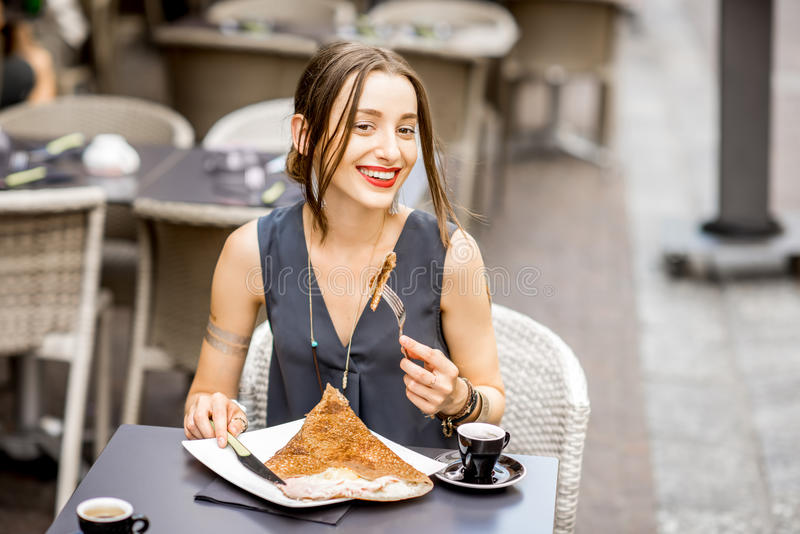 Woman eating galette meal at the restaurant in France. Young woman having a breakfast with french pancakes called galette sitting at the restaurant outdoors in stock images
