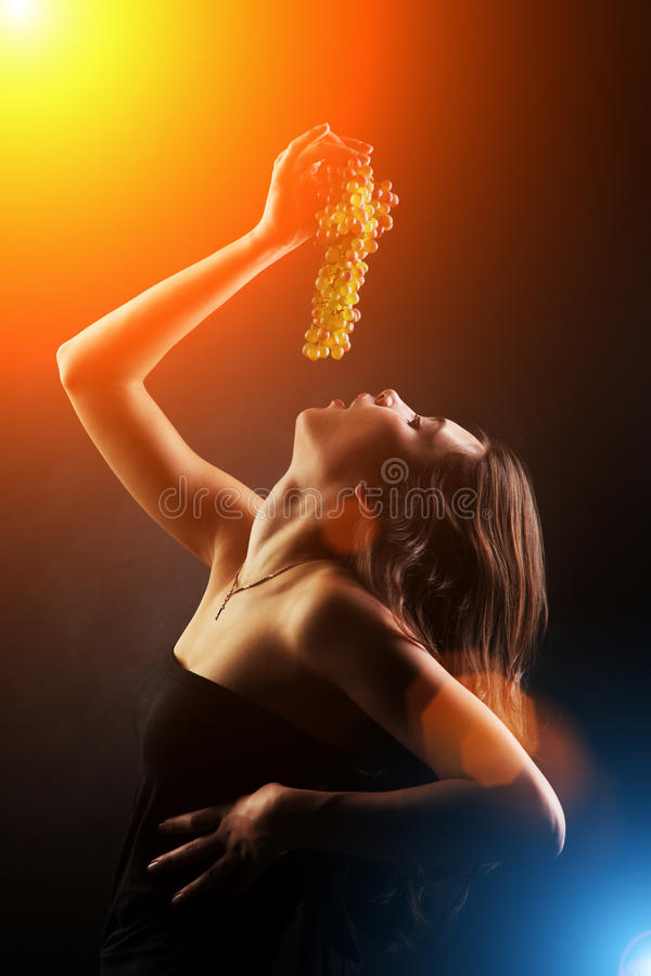 Woman eating grapes. Young woman eating bunch of grapes stock photography