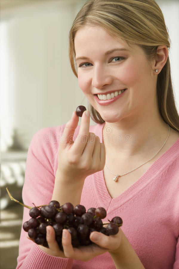 Download Woman Eating Grapes stock photo. Image of home, fruit - 14647222