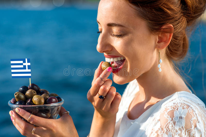 Woman eating greek olives stock photo