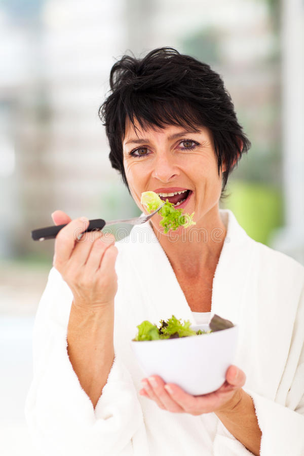 Woman eating green. Healthy middle aged woman eating green salad stock photography