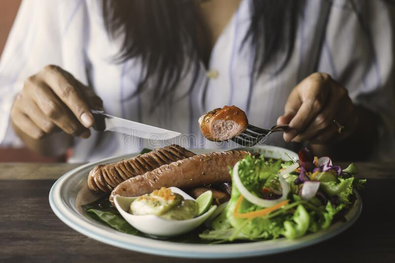 A woman eating grilled sausage, in morning stock photo
