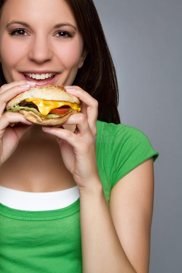 Woman Eating Hamburger. Beautiful young woman eating hamburger royalty free stock images