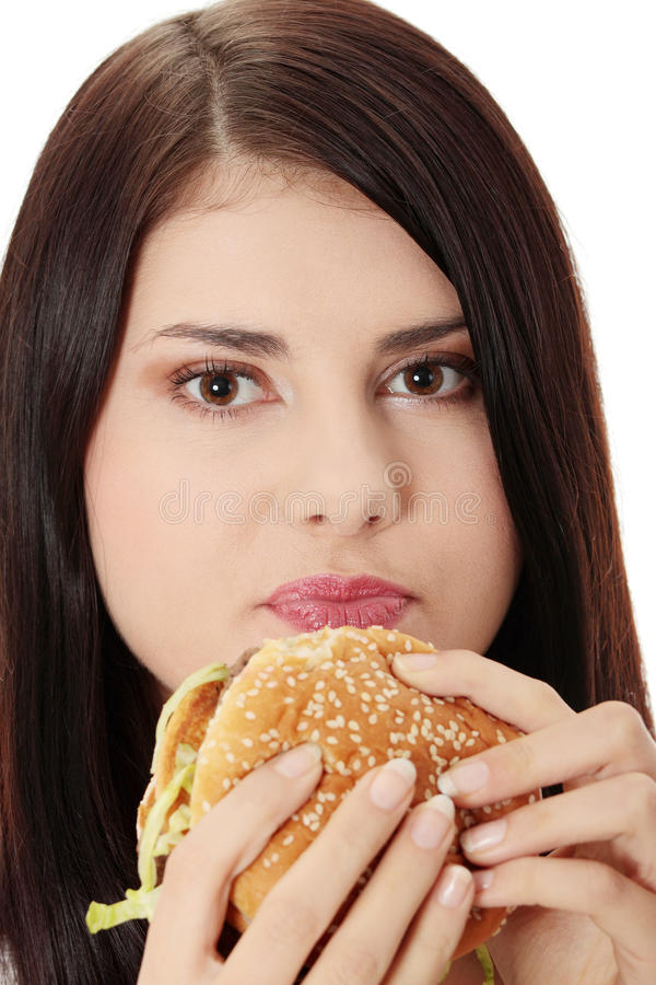 Woman eating hamburger. Beautiful caucasian woman eating hamburger. Isolated on white stock photo