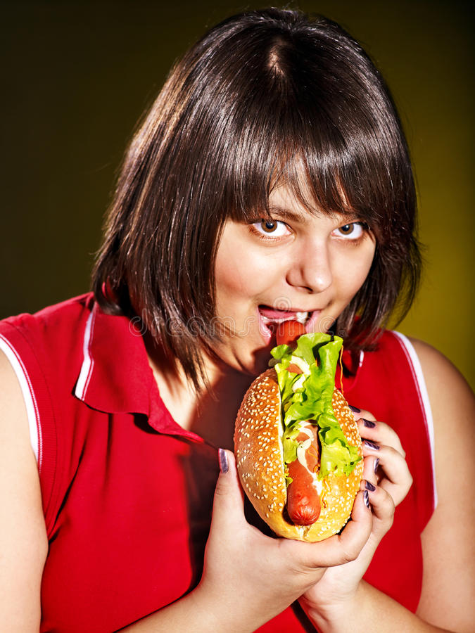 Woman eating hamburger. Overweight woman eating hamburger royalty free stock photo