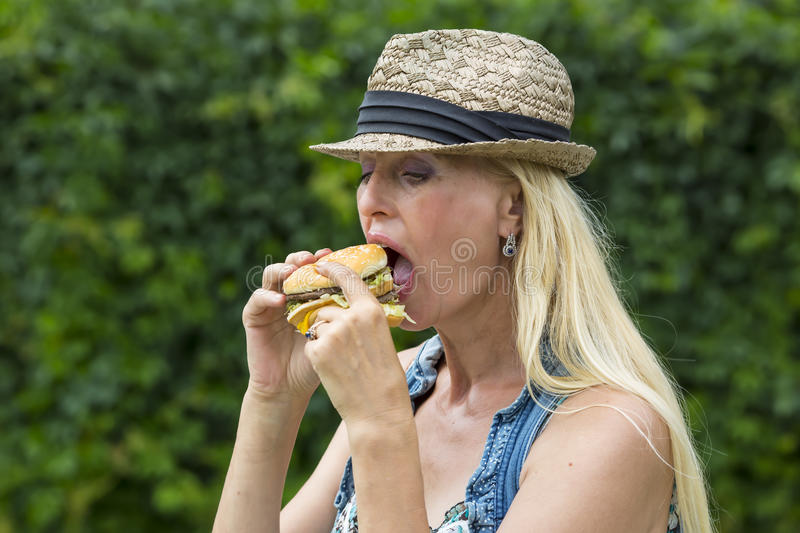 Woman eating a hamburger. Adult woman hippie woman eating a hamburger royalty free stock photos