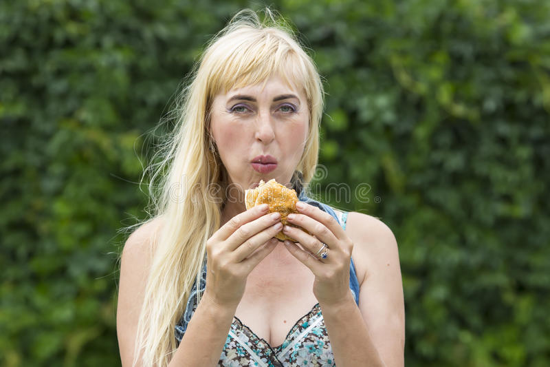 Woman eating a hamburger. Adult woman hippie woman eating a hamburger royalty free stock photography