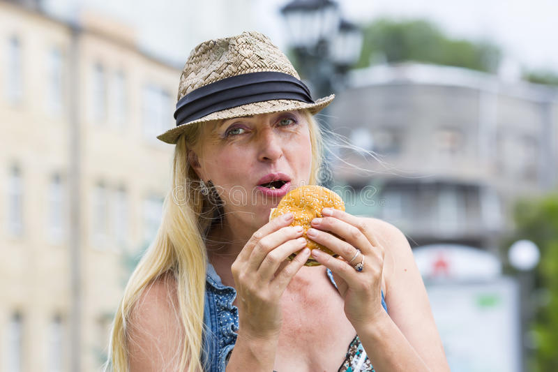 Woman eating a hamburger. Adult woman hippie woman eating a hamburger stock photography
