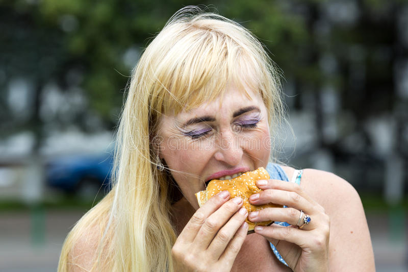 Woman eating a hamburger. Adult woman hippie woman eating a hamburger stock photos