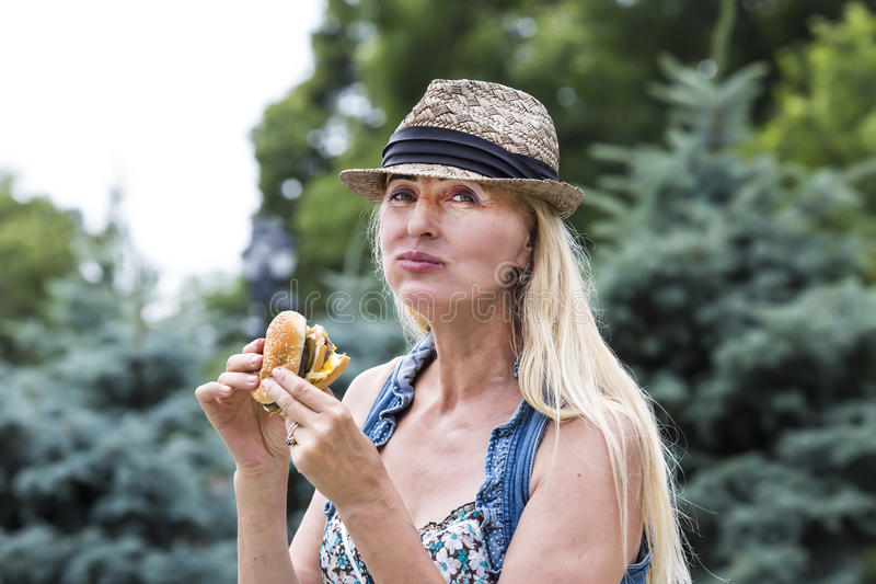 Woman eating a hamburger. Adult woman hippie woman eating a hamburger royalty free stock images