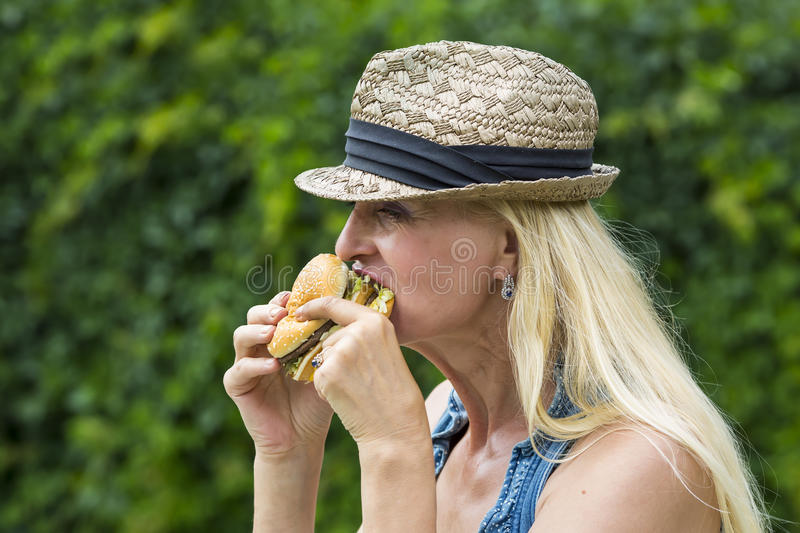 Woman eating a hamburger. Adult woman hippie woman eating a hamburger stock image