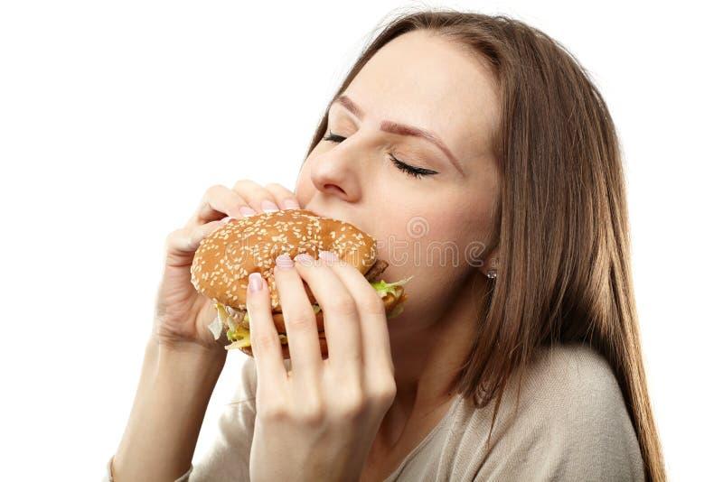 Woman eating hamburger. Closeup of a young caucasian woman eating a big hamburger, isolated on white background stock image