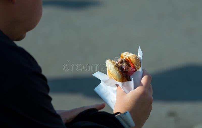 Woman eating hamburger outdoors. Woman eating the hamburger outdoors royalty free stock photography