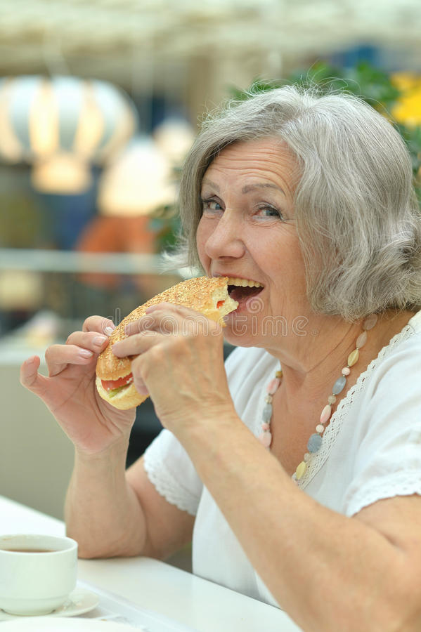 Woman eating hamburger. Portrait of a senior woman eating hamburger stock images