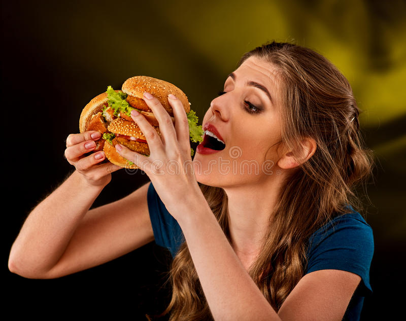 Woman eating hamburger. Student consume fast food on table. Cook teaches to cook and shares recipes. Girl eagerly eats junk alone without embarrassment royalty free stock photography