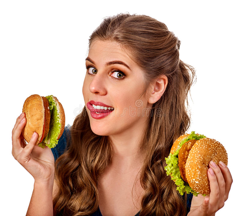 Woman eating hamburger. Student consume fast food on table. Teaches to cook and shares recipes. Girl eats junk alone without embarrassment. Use of semi royalty free stock image