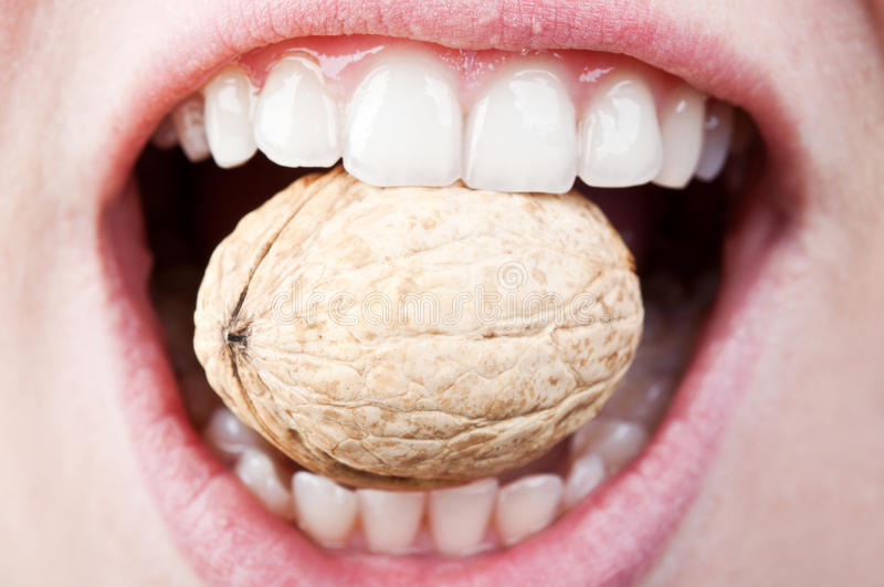Woman eating hard nut. A woman with a healthy and beautiful teeth eating hard nut royalty free stock photos