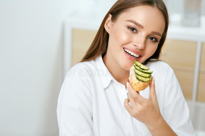 Woman Eating Healthy Diet Food. Happy Girl Eating Sandwich With Vegetables, Avocado Toast In Kitchen. Beautiful Smiling Female Eating Bread With Avocado For royalty free stock images
